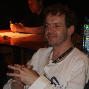 Na zdjęciu mężczyna w białej koszuli, siedzący w ciemnym pomieszczeniu
