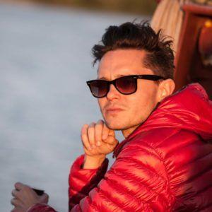 Na zdjęciu mężczyzna w przeciwsłonecznych okularach i czerwonej kurtce