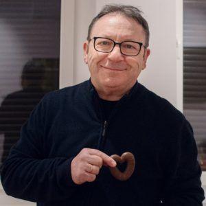 Na zdjęciu uśmiechnięty mężczyzna w okularach, z ciaskiem