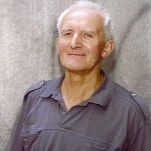 Na zdjęciu uśmiechnięty, siwy mężczyzna na szarym tle